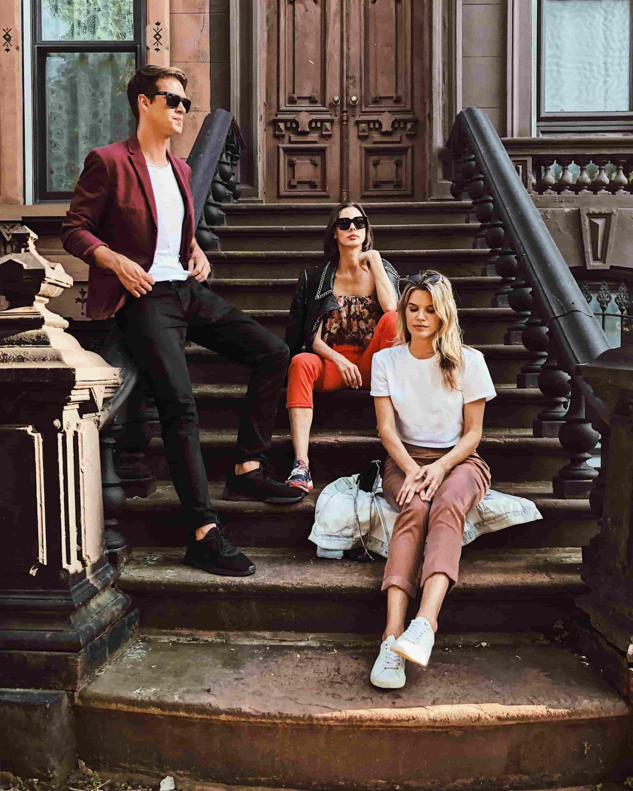 Three friend sitting on staircase outside of house in Bedford-Stuyvesant, Brooklyn, New York City