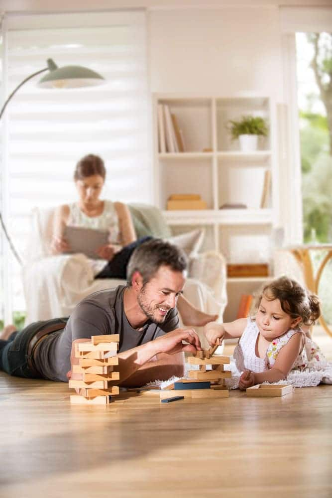 Happy man lying on clean floor while playing game with daughter