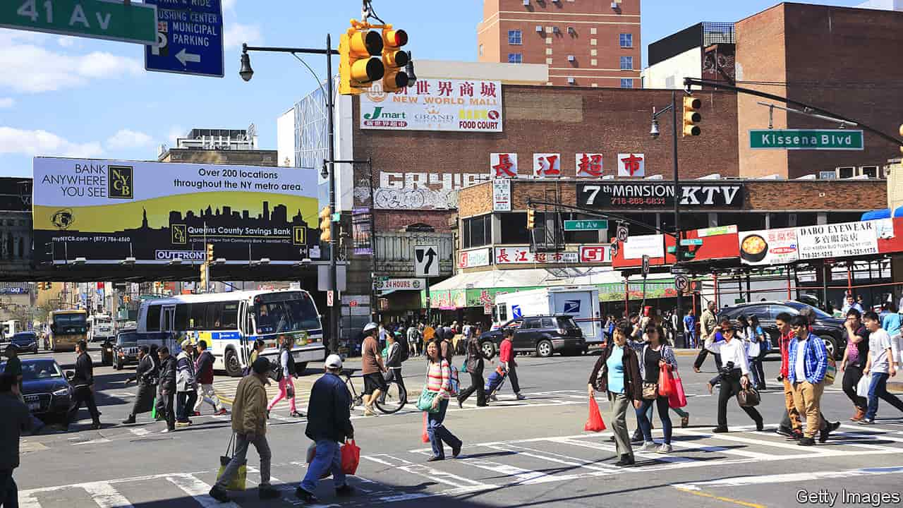People walking across large intersection at Kissena Blvd in Queens, New York City