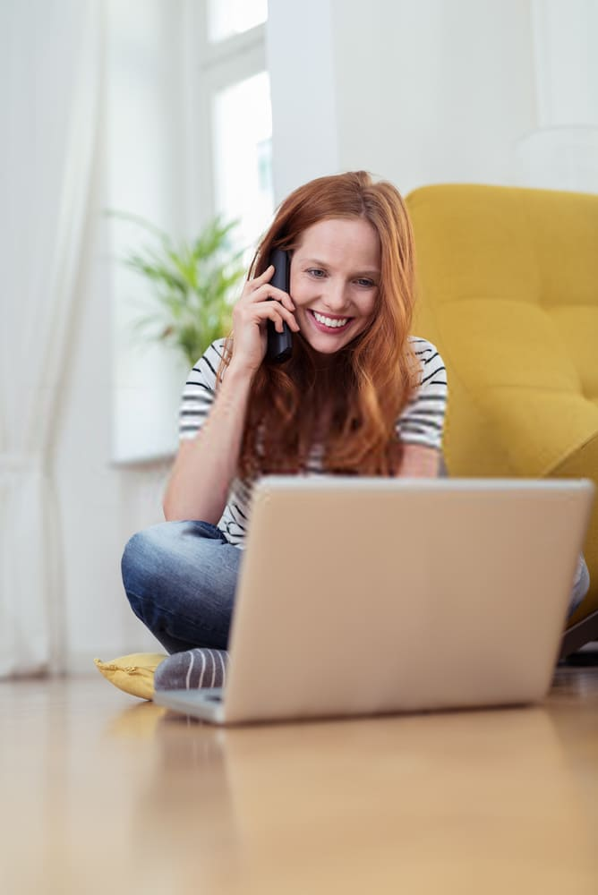 Woman on phone and laptop scheduling a cleaning service appointment